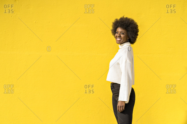 African American woman joyful laughing with yellow wall on background