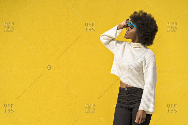 Black woman with curly hair smiles as she looks down from her blue glasses