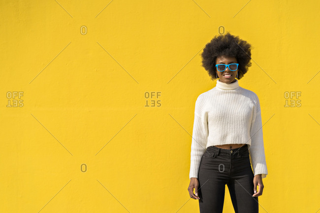 Black woman joyful with Afro hair wearing blue sunglasses with yellow wall on background