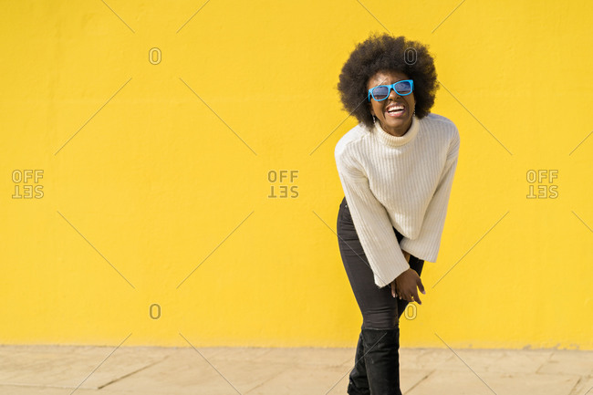 Young cool woman with Afro hair wearing blue sunglasses laughing out loud with yellow wall on background