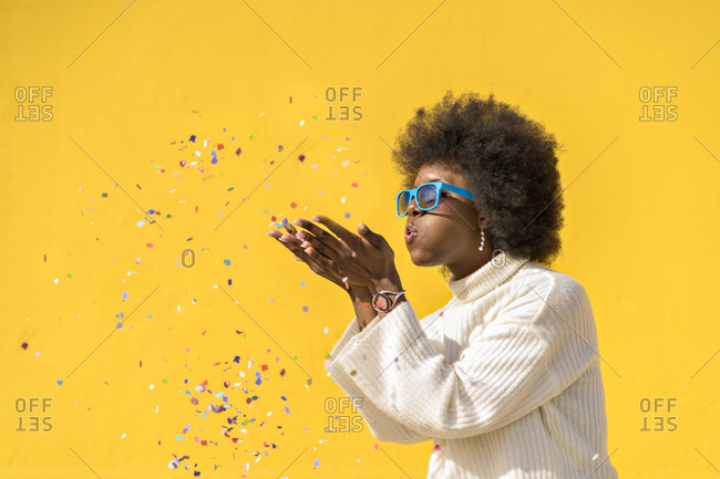 Young black woman with curly hair blowing confetti on yellow background
