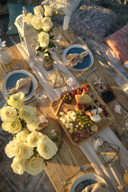 High angle view of fresh dinner served on dining table at beach during beautiful sunset- Nayarit- Mexico