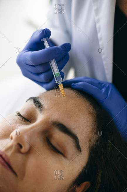 Woman receiving hyaluronic acid injection in medical practice
