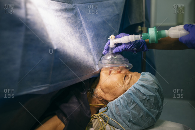 Anesthetist applying anesthesia machine to patient in operating room