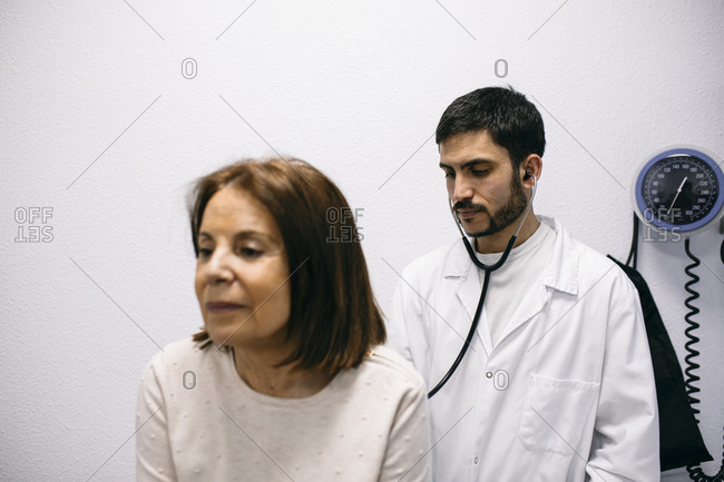 Doctor examining patient with a stethoscope in medical practice