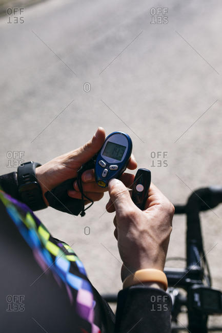 Close-up of diabetic cyclist checking his sugar level