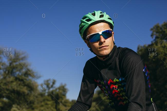 Portrait of confident cyclist under blue sky