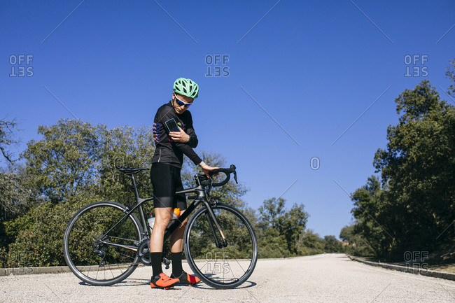 Diabetic cyclist checking his sugar level during a break on country road