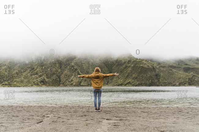 Full length of female tourist with arms outstretched standing at lakeshore in Sao Miguel Island- Azores- Portugal