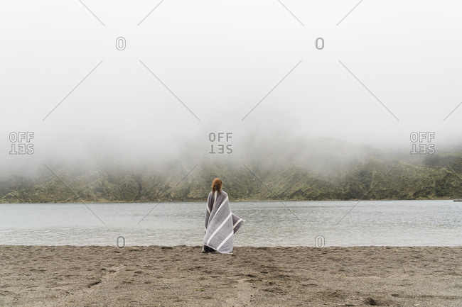Woman wrapped in blanket standing at lakeshore in Sao Miguel Island- Azores- Portugal