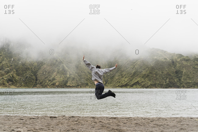 Full length of man jumping in mid-air while enjoying vacation at Sao Miguel Island- Azores- Portugal
