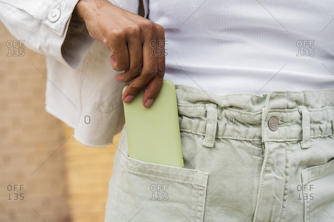 Close-up of woman putting smartphone into her pocket