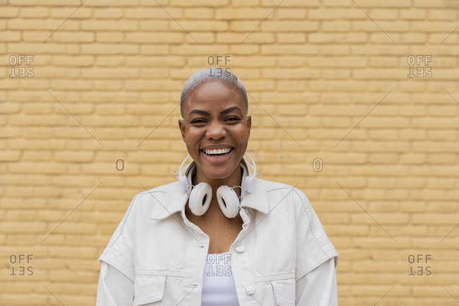 Portrait of happy woman with headphones outdoors