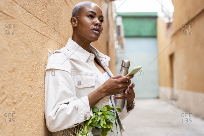 Woman leaning against a wall with thermos flask- groceries and smartphone