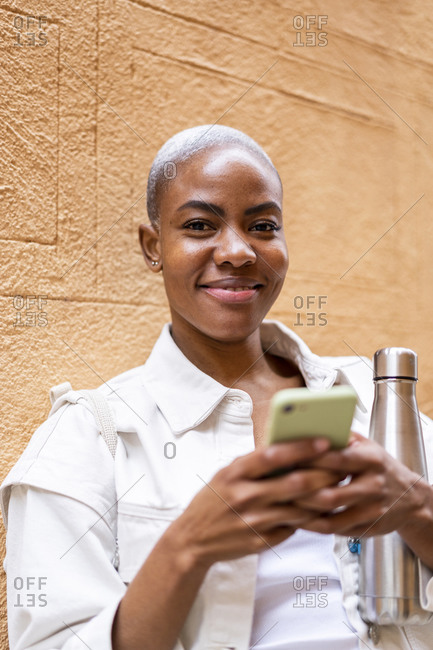 Portrait of smiling woman leaning against a wall with thermos flask and smartphone