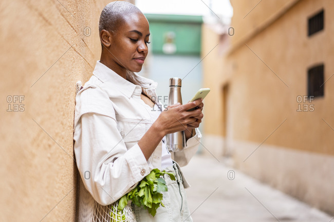 Woman leaning against a wall with thermos flask and groceries using smartphone