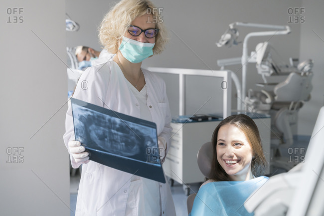 Young woman getting dental treatment in clinic- doctor explaining x-ray