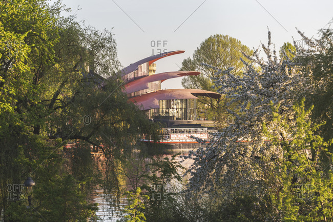 April 22, 2019: Germany- Brandenburg- Potsdam- Cherry blossoms blooming on bank of Havel river with Hans Otto Theater in background