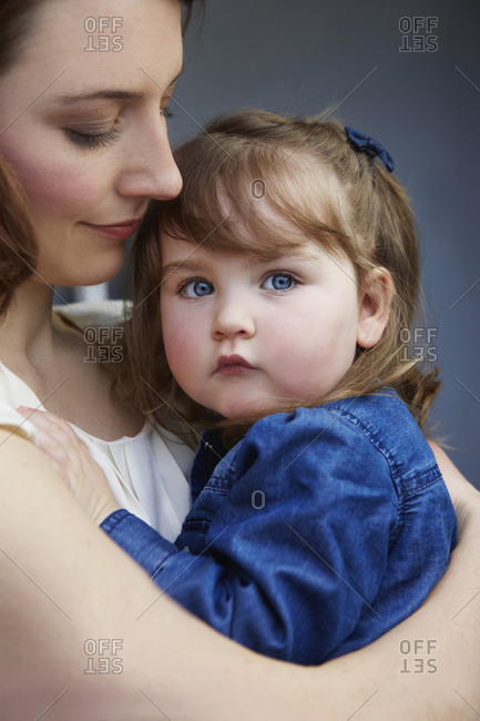 Portrait of toddler girl in her mother's arms