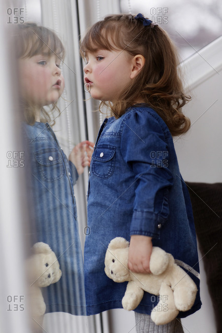 Portrait of curios toddler girl with teddy bear watching something