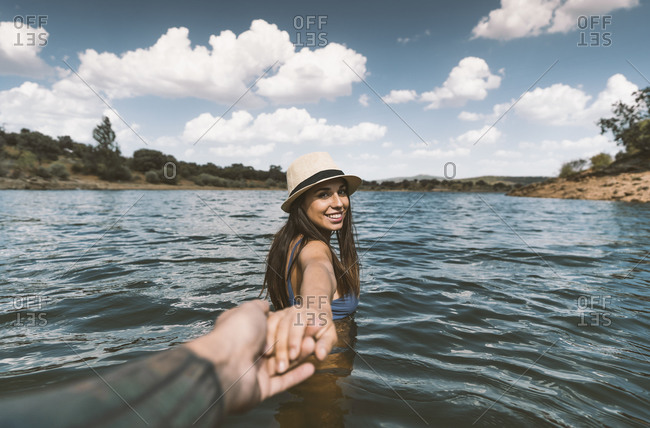Portrait of happy young woman bathing in a lake holding boyfriend's hand