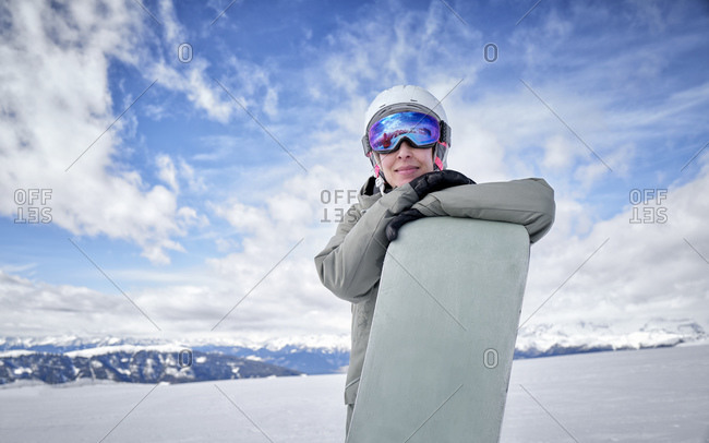 Smiling woman leaning on snowboard