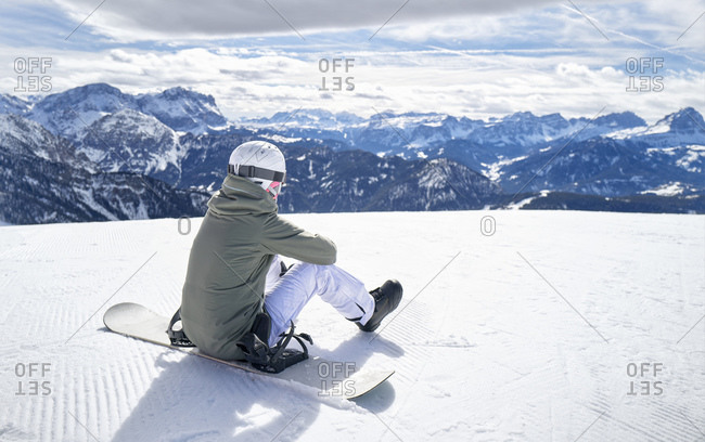 Smiling woman sitting with snowboard on viewpoint and enjoying view at distance