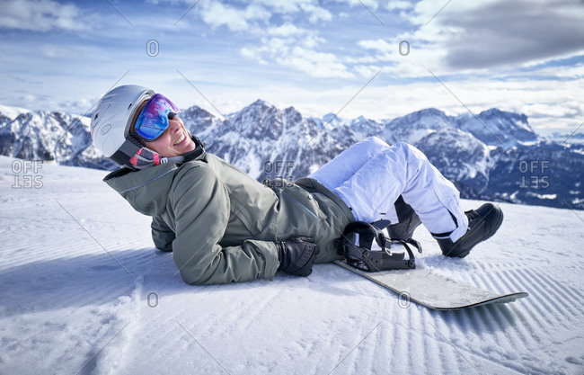 Smiling woman sitting with snowboard on viewpoint and looking at camera