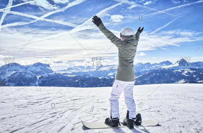 Mature woman with snowboard on ski slope with raised arms