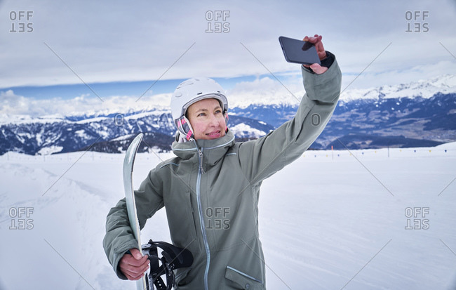 Smiling female snowboard taking a selfie with her smartphone