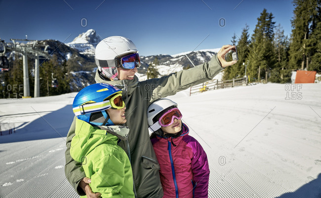 Mother with her children- taking a selfie on ski slope