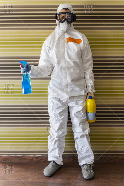 Woman wearing protective clothes- sanitizing her home