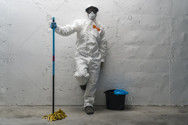 Woman with cleaning equipment- wearing protective clothing- leaning against wall