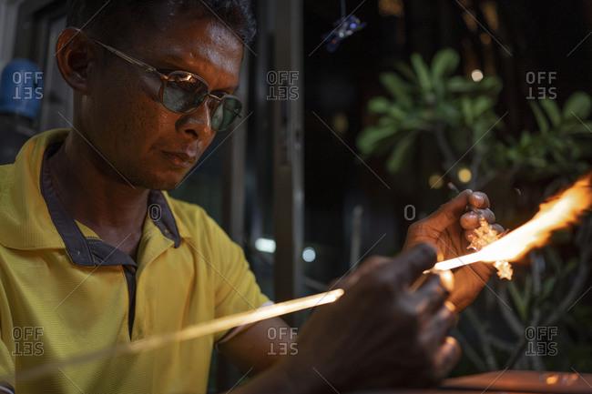 Senior man forming melting glass