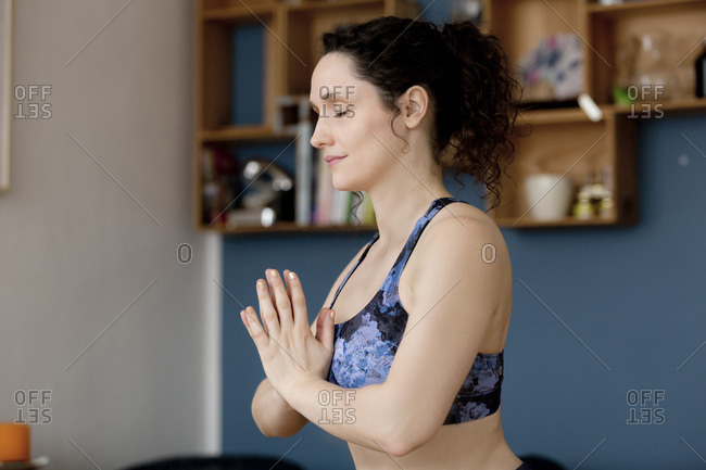 Young woman with closed eyes and anjali mudra in yoga pose at home