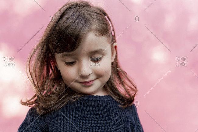 Portrait of smiling little girl in front of  pink background