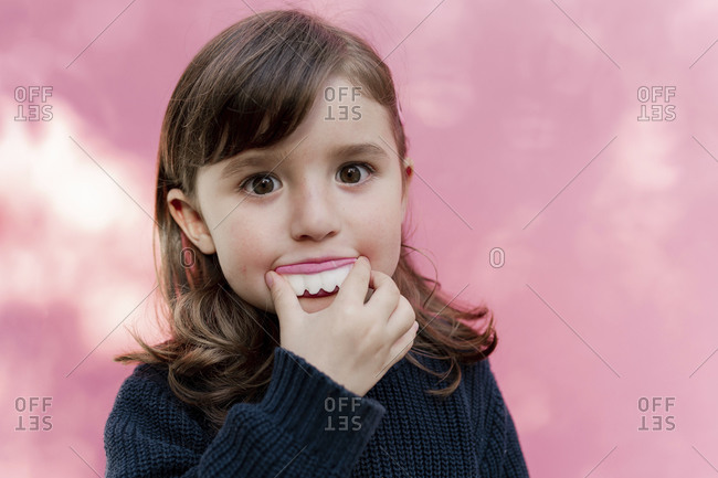 Portrait of little girl with false candy teeth in front of  pink background