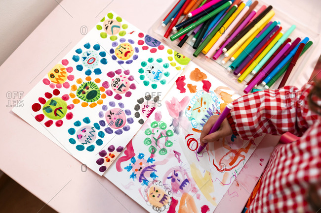 Little girl drawing  ugly viruses with color markers at home