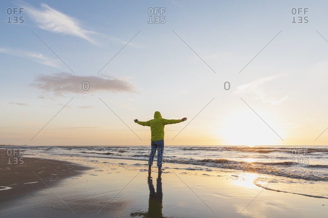 Senior man with arms outstretched standing on shore at beach during sunset- North Sea Coast- Flanders- Belgium