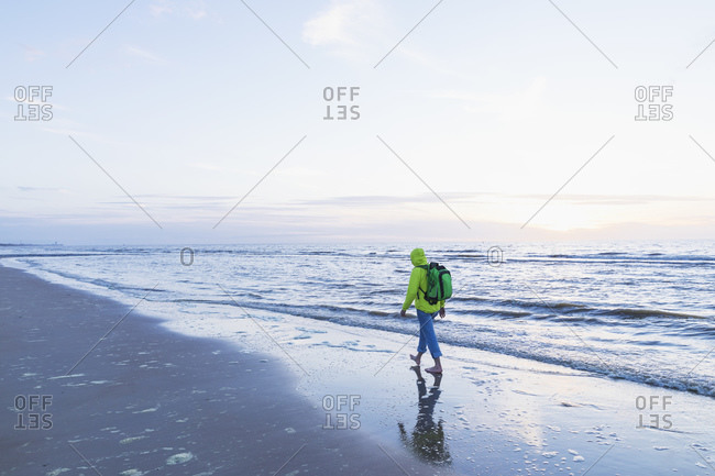 Retired senior man with backpack walking on shore at beach during sunset- North Sea Coast- Flanders- Belgium