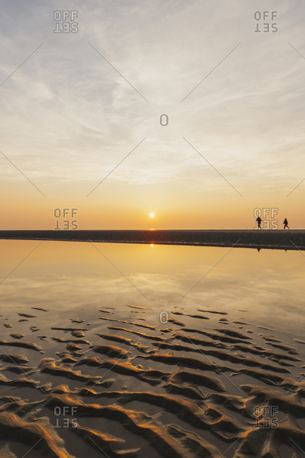 Distant view of silhouette people walking at beach against sky during sunset- North Sea Coast- Flanders- Belgium