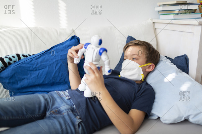 Boy with mask playing in his room during the corona crisis with his new- only friend- a robot