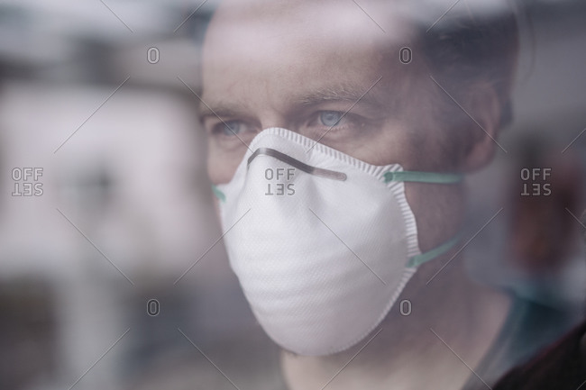 Portrait of man wearing protective mask behind windowpane