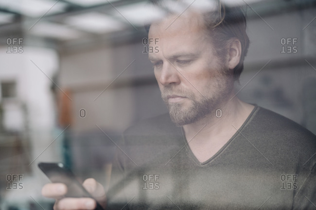 Portrait of businessman using cell phone behind windowpane