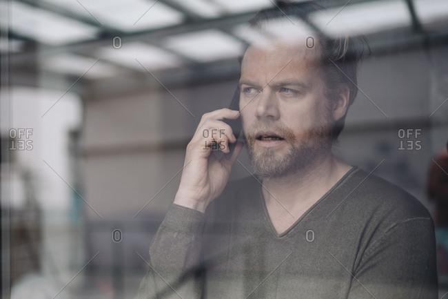 Portrait of businessman on the phone behind windowpane