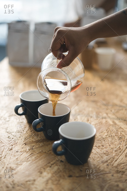 Woman pouring coffee into cup in a coffee roastery