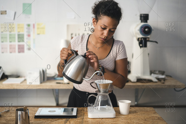Woman working in a coffee roastery preparing fresh filtered coffee