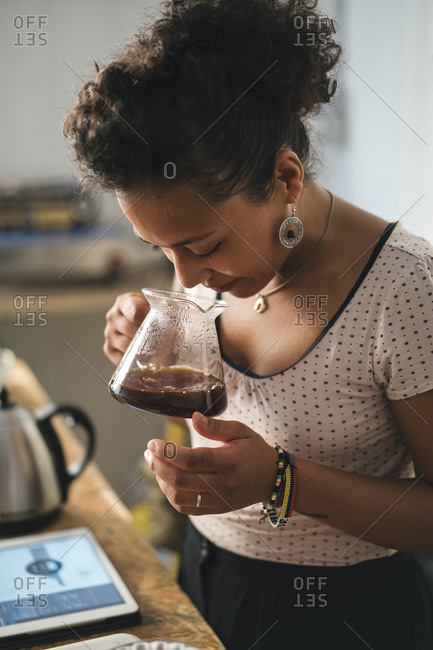 Woman working in a coffee roastery smelling at coffee