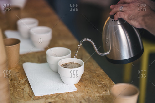 Close-up of man working in a coffee roastery pouring hot water into coffee cups