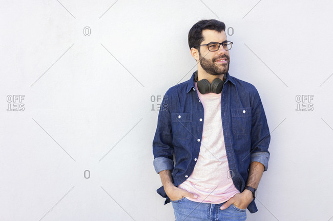 Portrait of smiling man with wireless headphones looking at distance